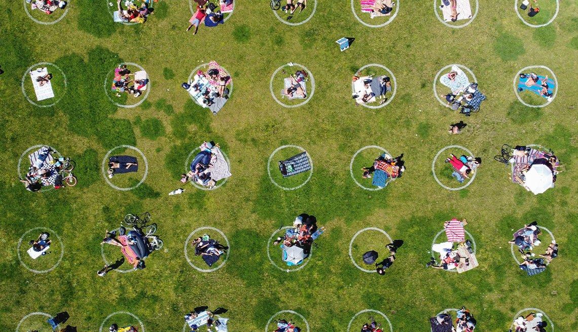 Foto aérea de personas en un parque cubierto de hierba dentro de círculos de distanciamiento social pintados sobre el césped