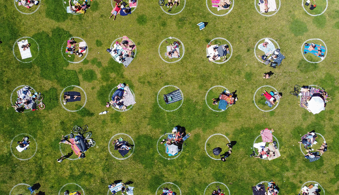 aerial photo of people in a grassy park staying within social distancing circles painted on the grass