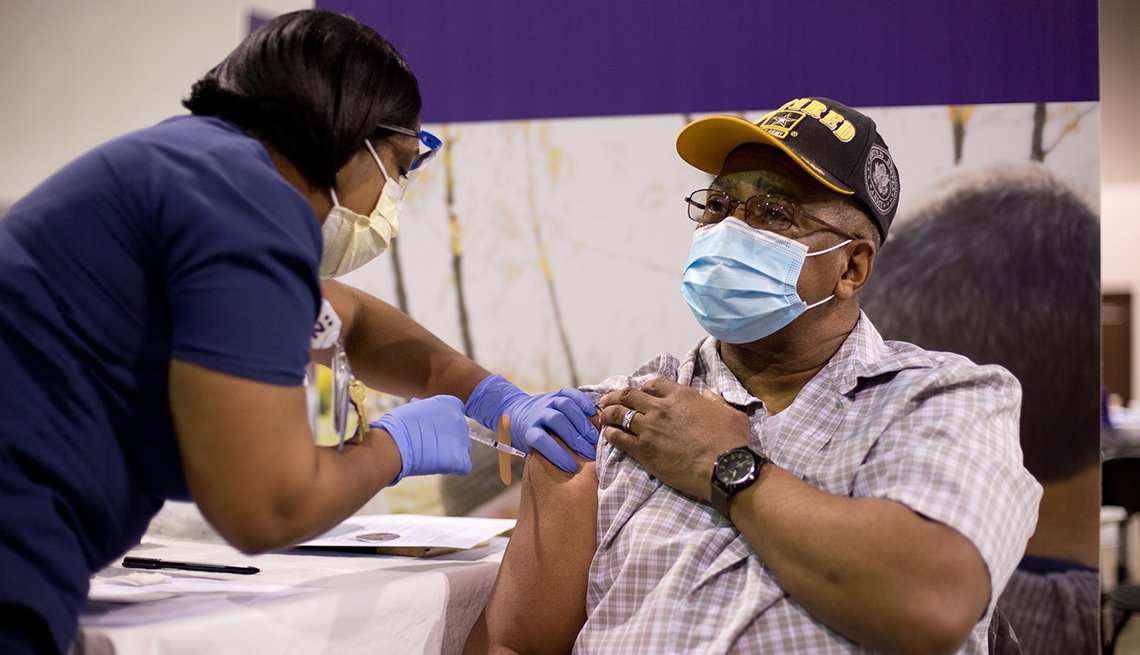 a health professional administers the covid vaccine to a retired army captain