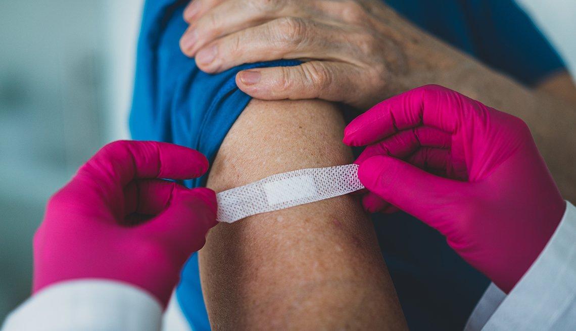 Doctor colocando una tirita en el brazo de un paciente.