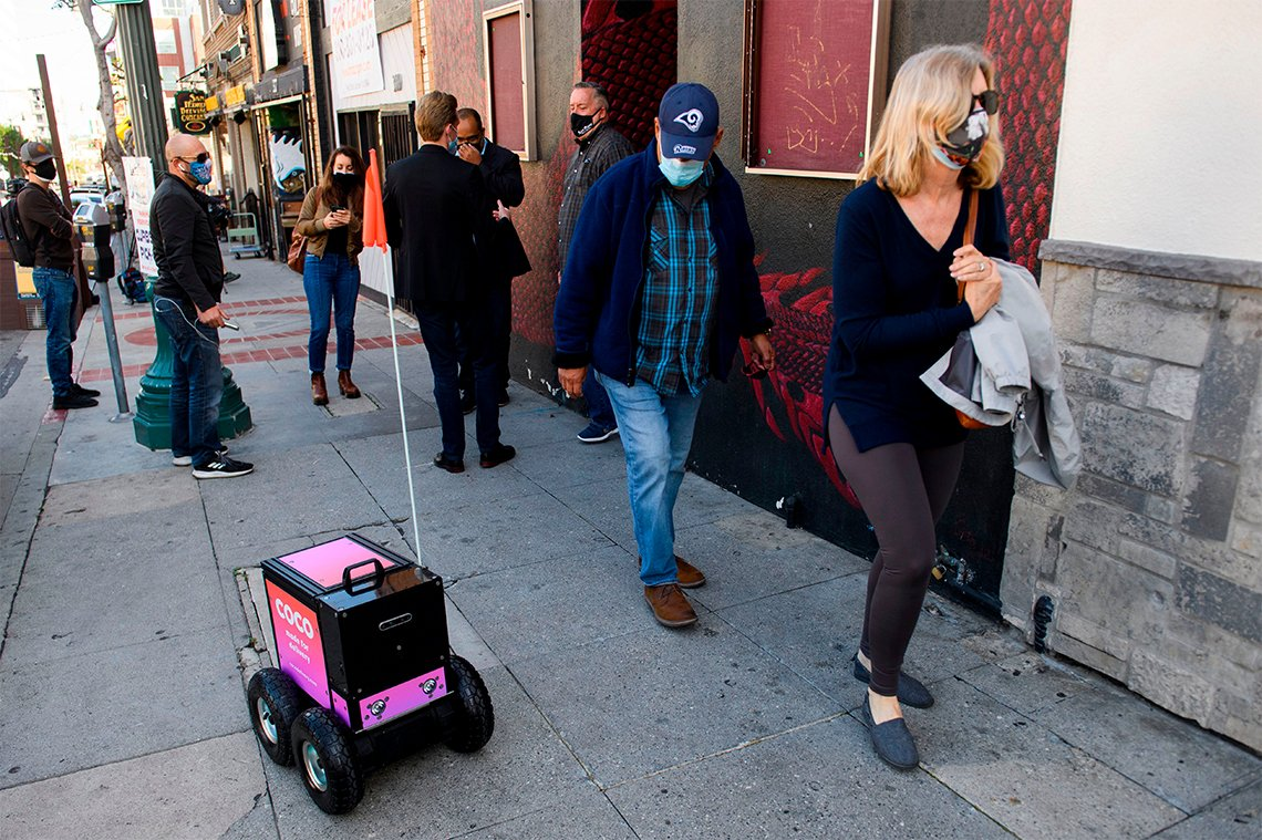 a remote controlled delivery robot on a sidewalk amongst pedestrians