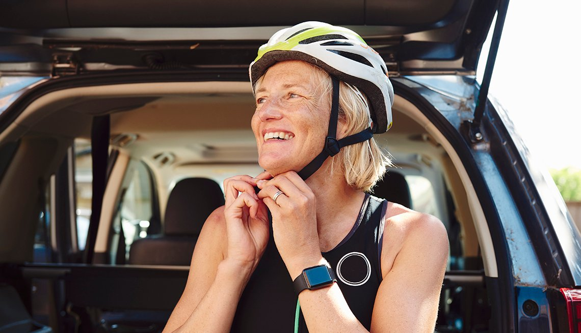 Una mujer se ajusta un casco antes de correr bicicleta