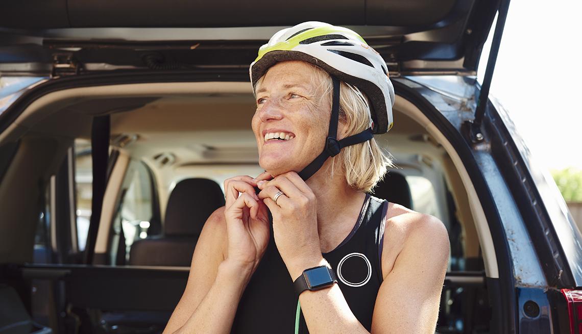 Woman putting on her bike helmet.