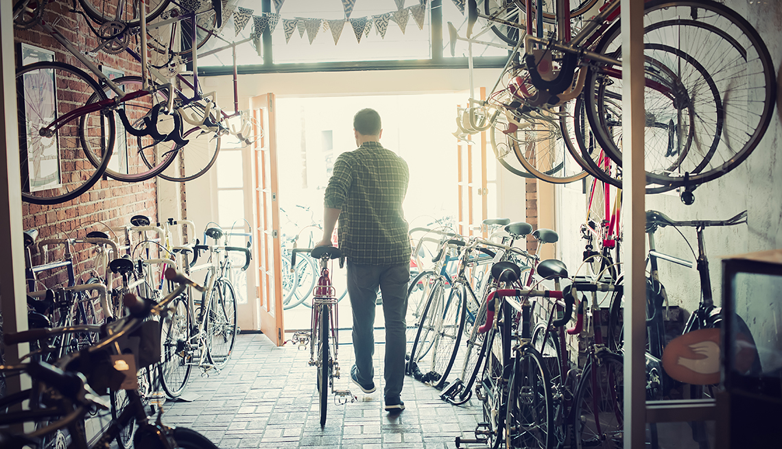 Man walking out of a bicycle shop with a new bike.