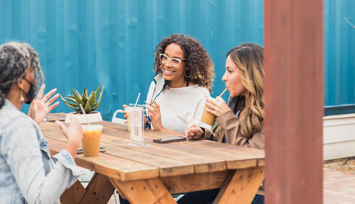 Amistades conversan en una mesa mientras toman un café