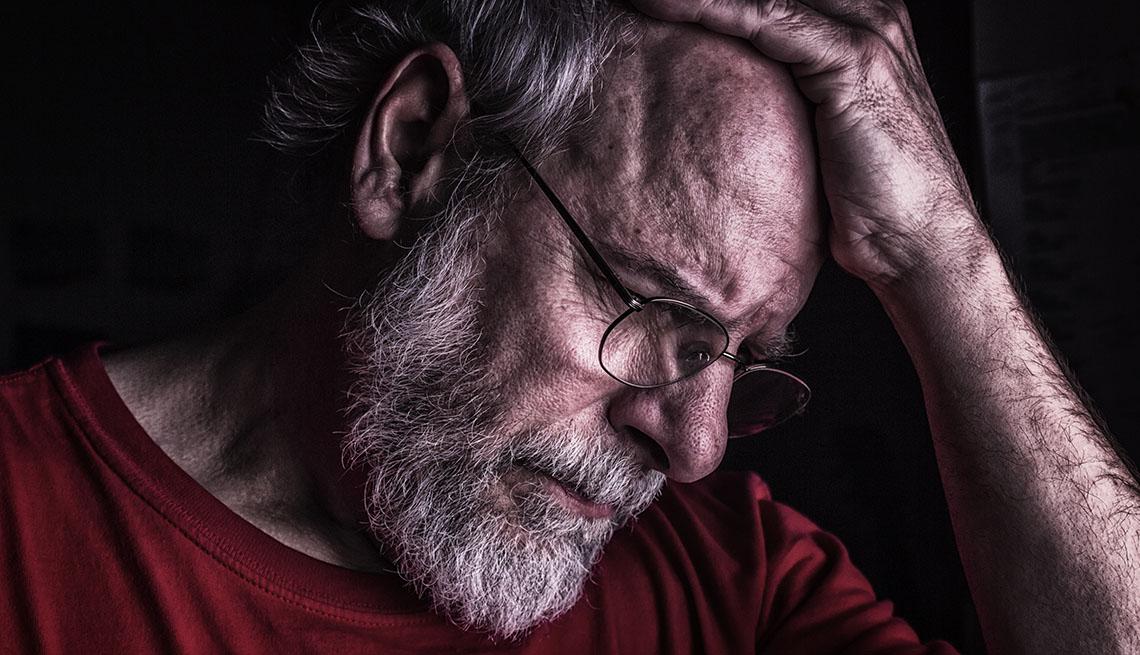 Hombre con su mano en la cabeza, deprimido