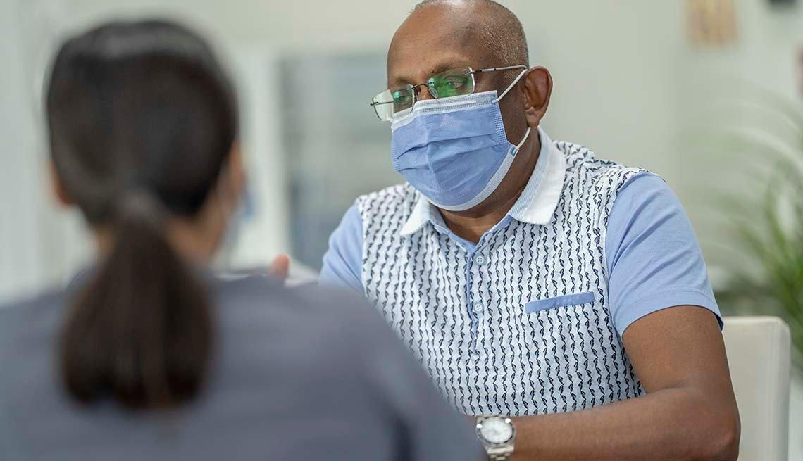 Un hombre, usando mascarilla, consulta a su médico