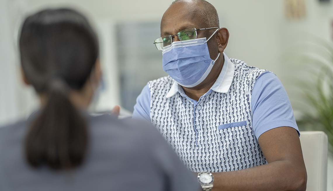 a masked patient speaks with a medical provider