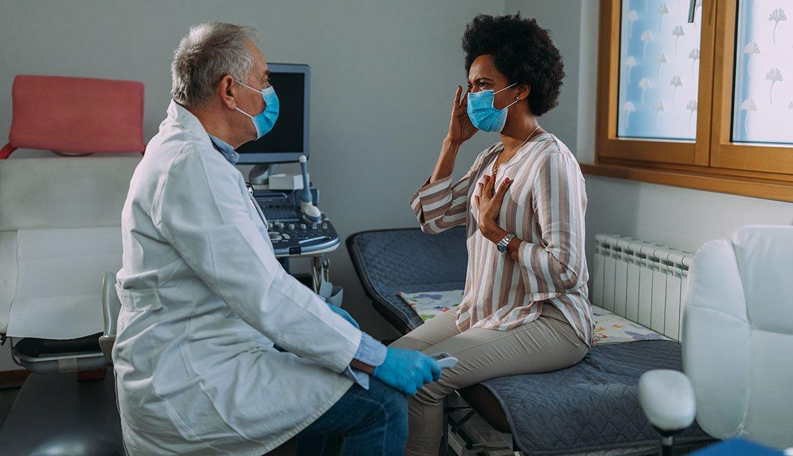Un médico examina a una paciente que usa mascarilla