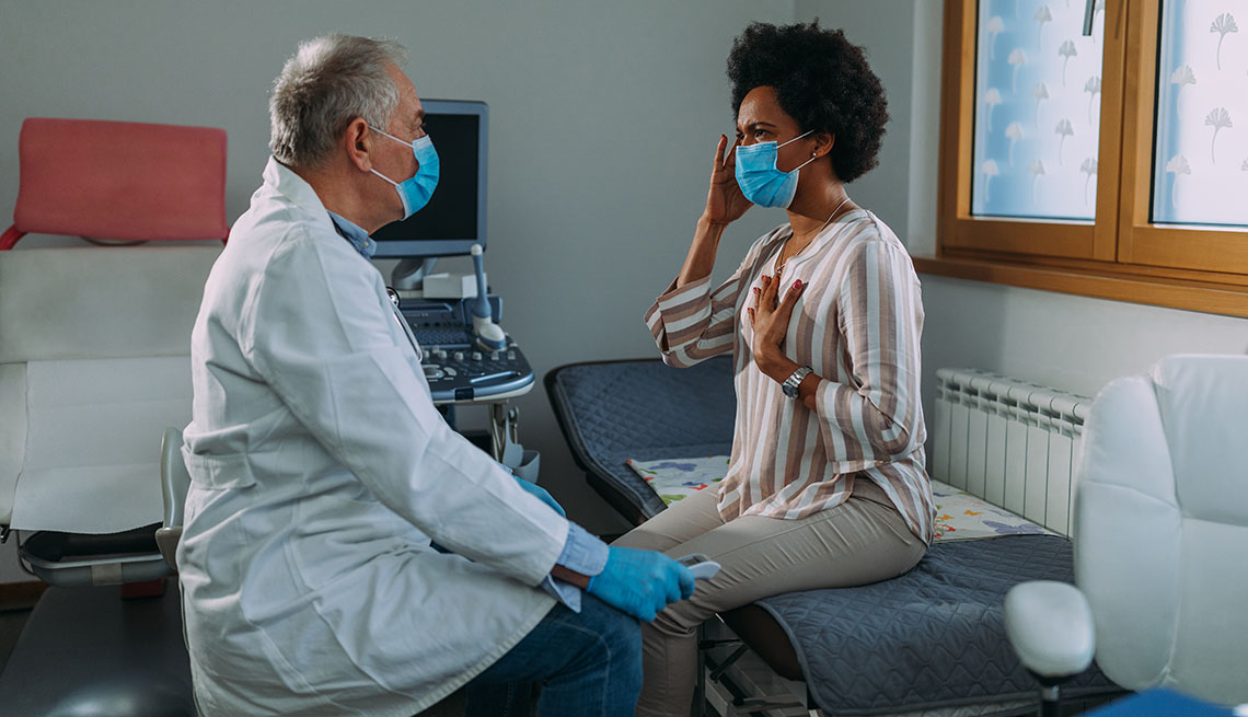 masked doctor examining masked patient