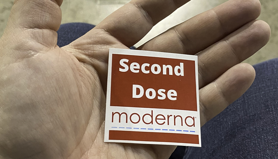 person holing a sticker that says moderna second dose