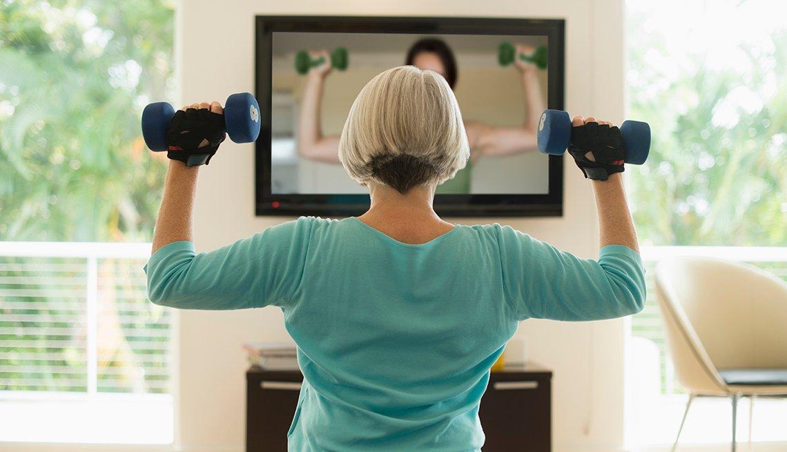 Una mujer hace ejercicios en la sala de su casa mientras ve un video en la TV