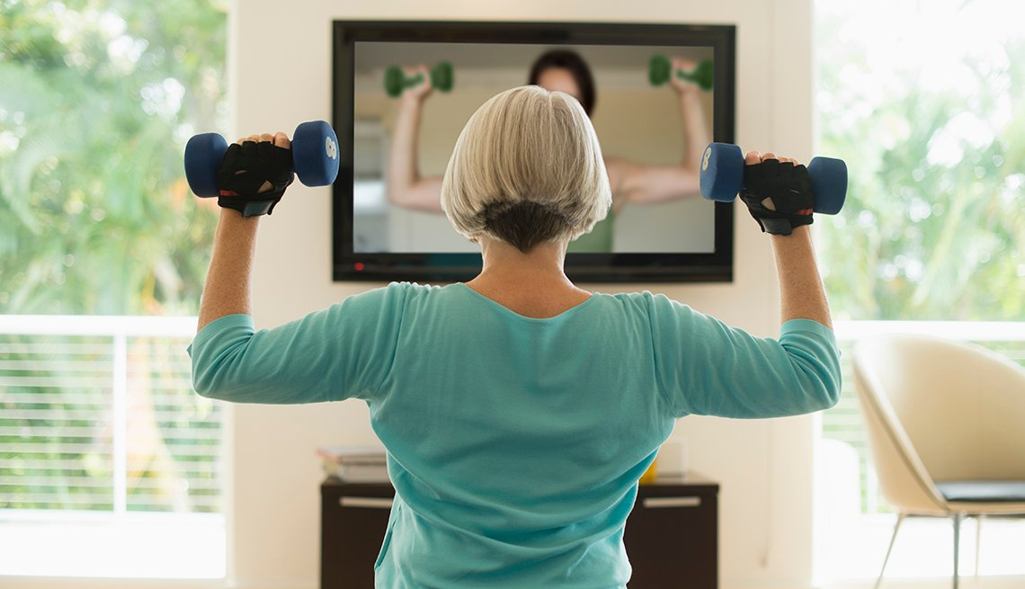 Woman watching exercise video and lifting weights.