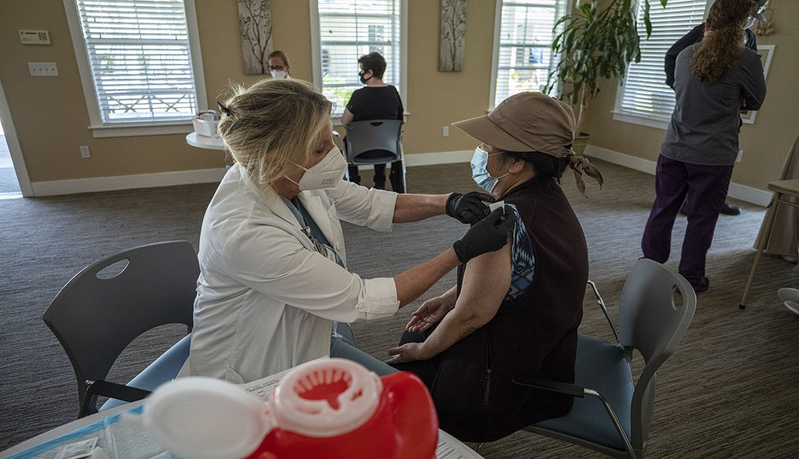 A healthcare worker wearing a protective mask and gloves administers a dose of the Johnson & Johnson Janssen Covid-19 vaccine.