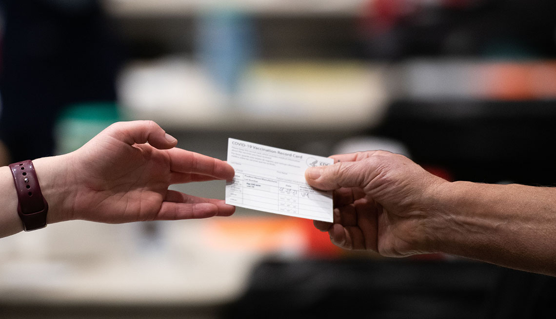 A patient receives a card showing when they received their first dose of the Pfizer Covid-19 vaccine.