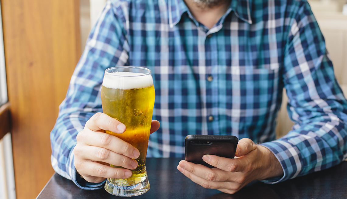 man holding a beer and looking at his smartphone