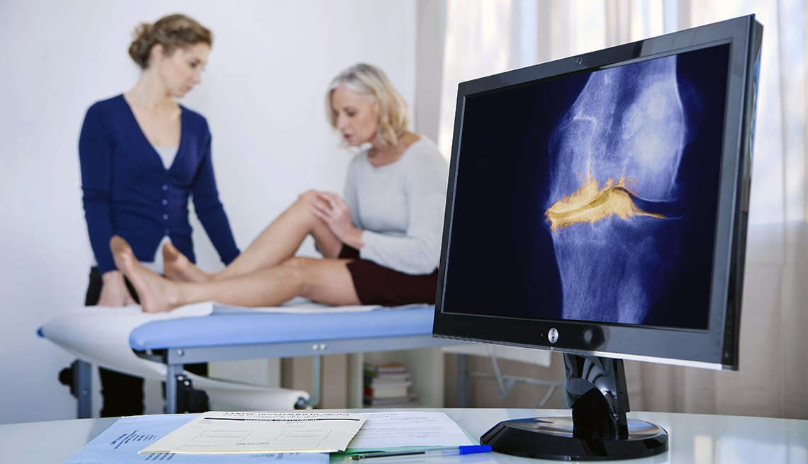 A bone scan display of a knee with arthritis in the foreground, while a woman in medical exam is explaining pain to health care provider in background.