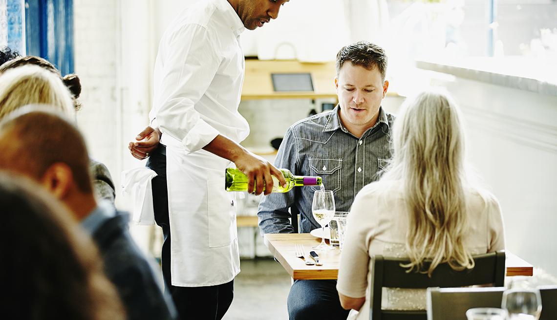 Mesero le sirve vino a una pareja sentada en una mesa en un restaurante