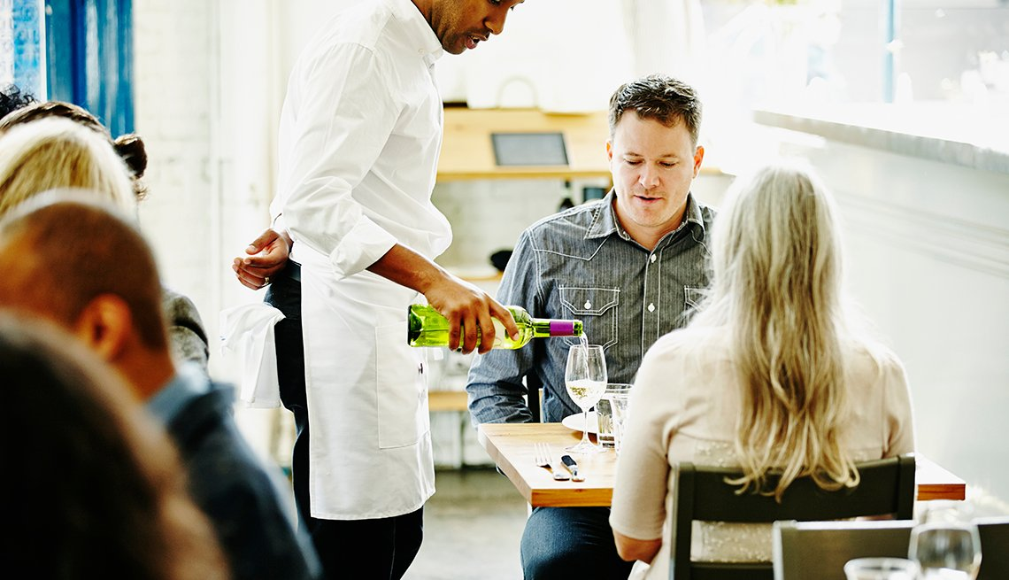 waiter pouring glass of wine for couple dining together in restaurant