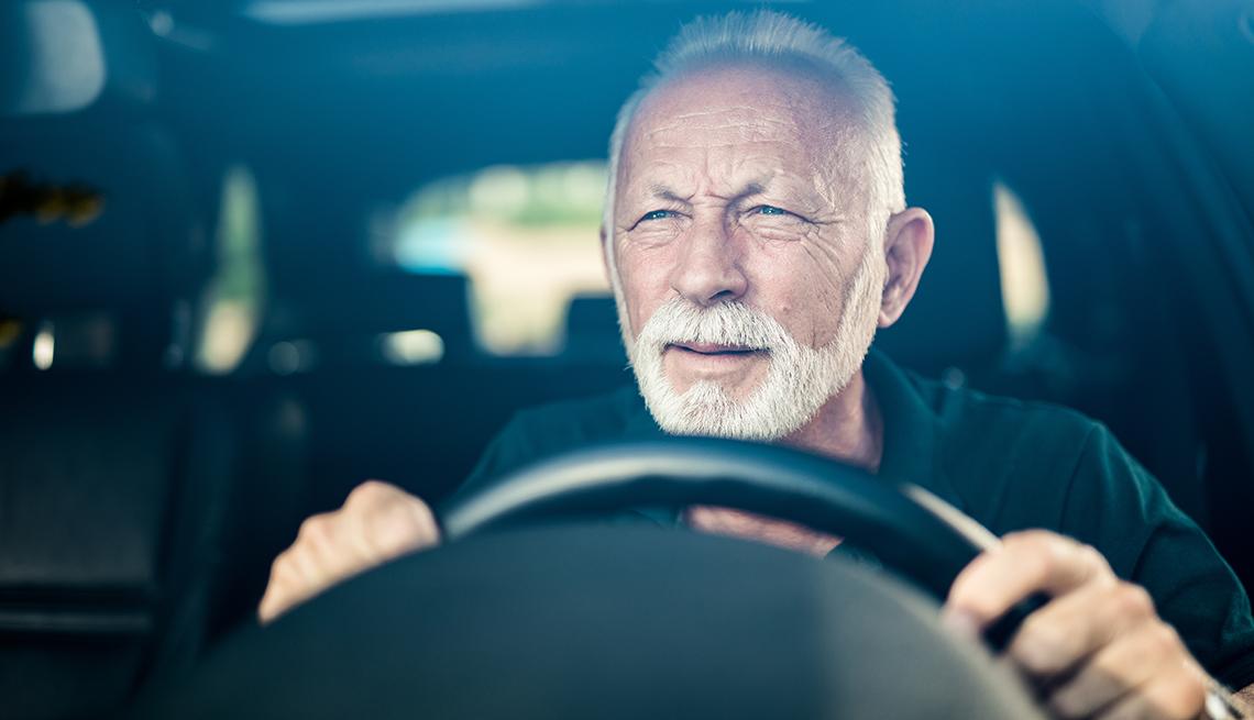 Un hombre entrecerrando los ojos mientras conduce de noche