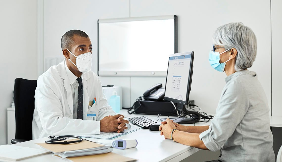 masked medical provider and patient in office setting