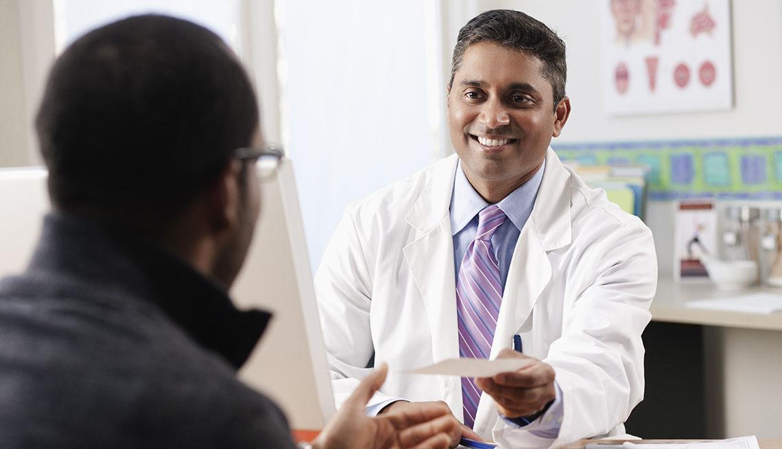 smiling doctor hands patient a prescription