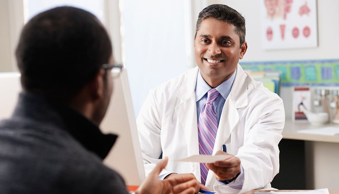 smiling doctor hands patient a prescription
