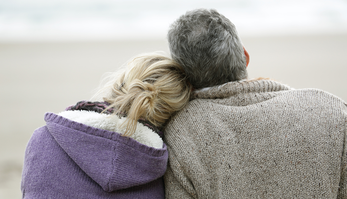 man and woman cuddling on the beach, looking at the ocean