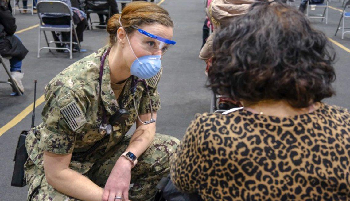 Mujer militar habla con una paciente en una clínica