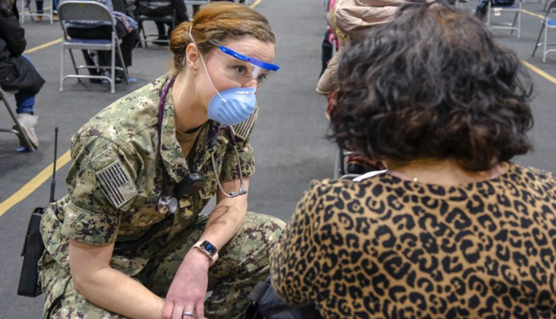 A member of the military talks with a woman at a clinic