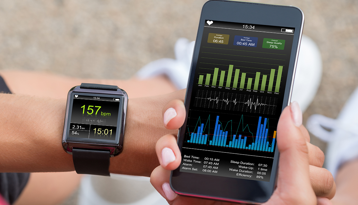 A person looks at a smartphone and a smartwatch