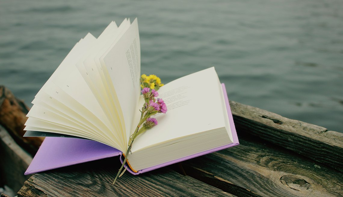 A book of poetry with flowers as a bookmark, with water in the background