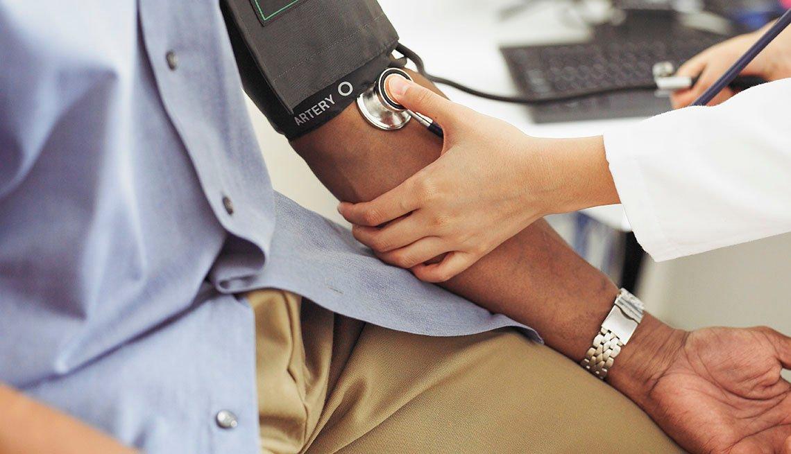 Una enfermera toma la presión de un paciente