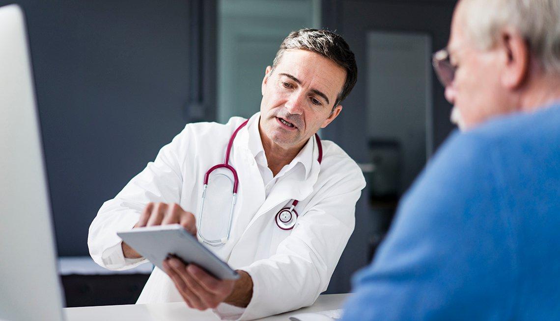 Un médico le muestra información en una tableta a un paciente