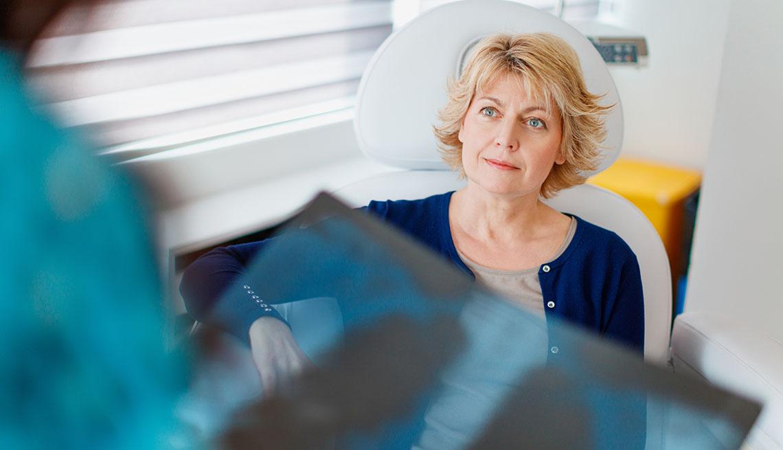 Una paciente sentada en un consultorio mientras su médico sostiene los resultados de unos rayos-x