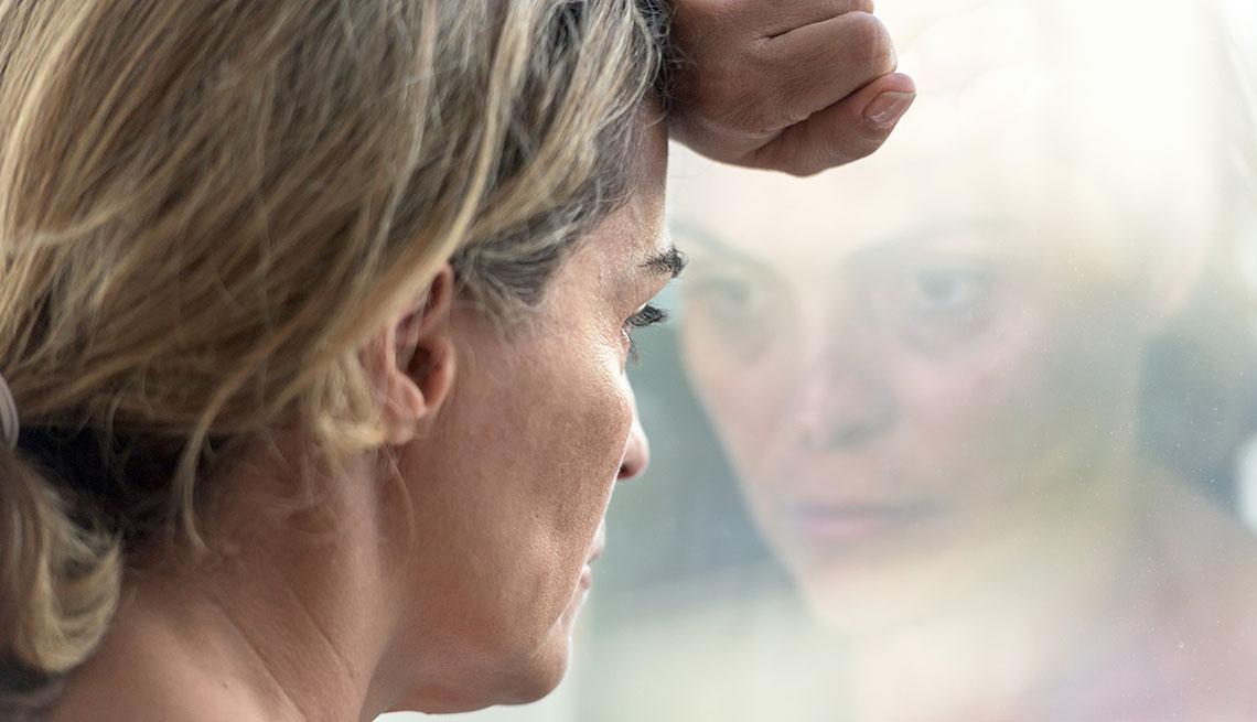 Una mujer, que luce deprimida, mira por una ventana