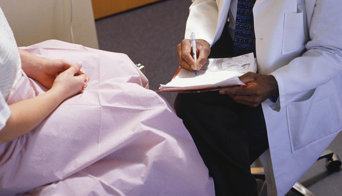 Un doctor toma notas mientras atiende a su paciente