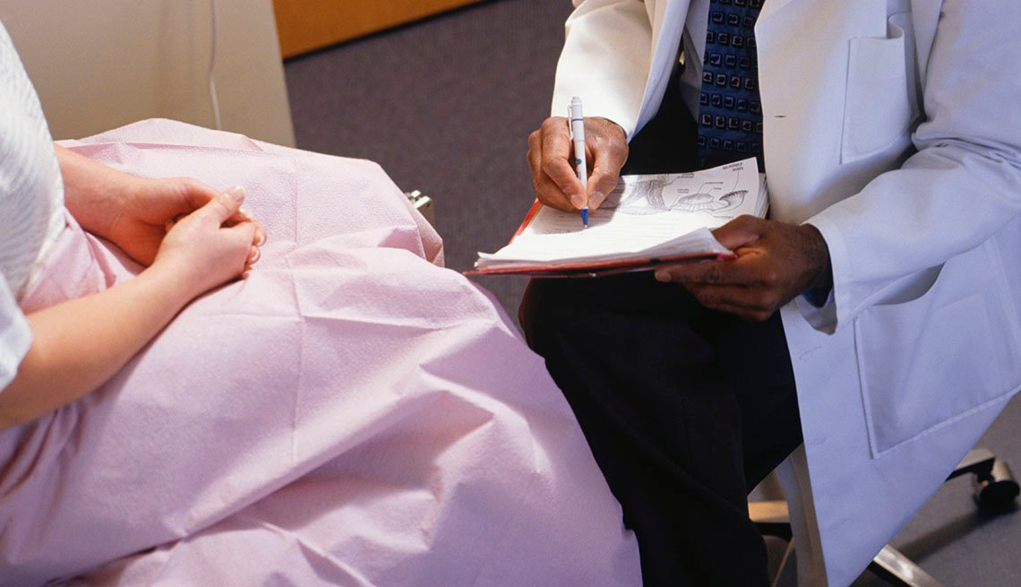 doctor writes on pad while talking with a female patient