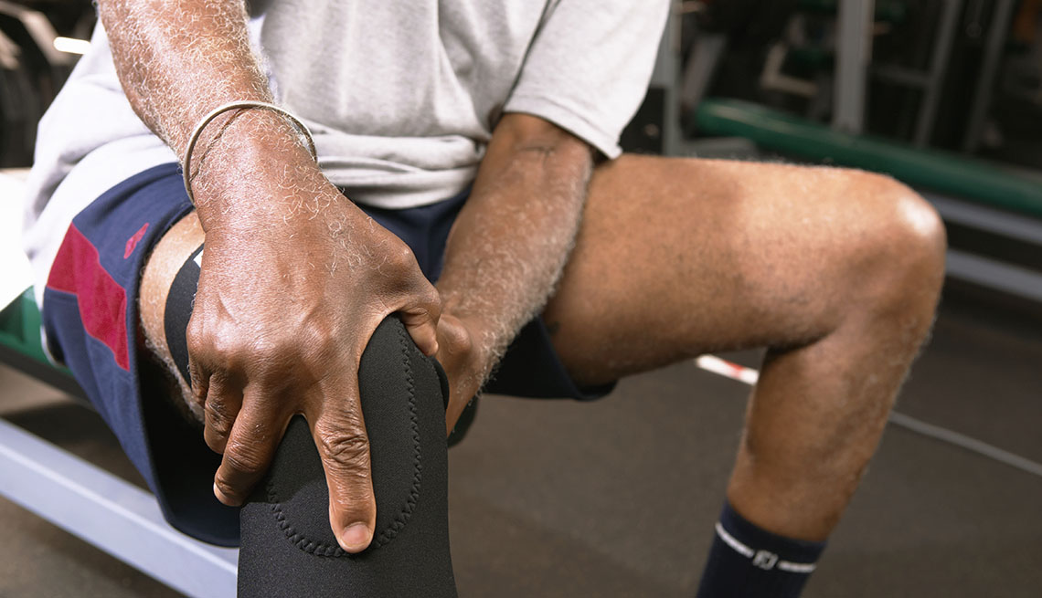 man working out holds his knee