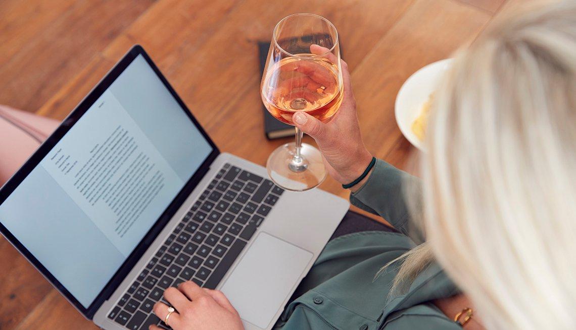 Una mujer trabaja desde su casa en una computadora, mientras sostiene una copa de vino