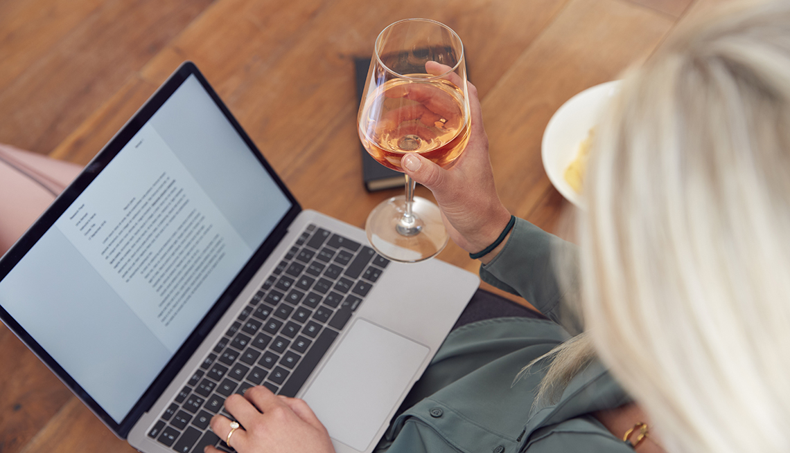woman working from home, drinking a glass of wine