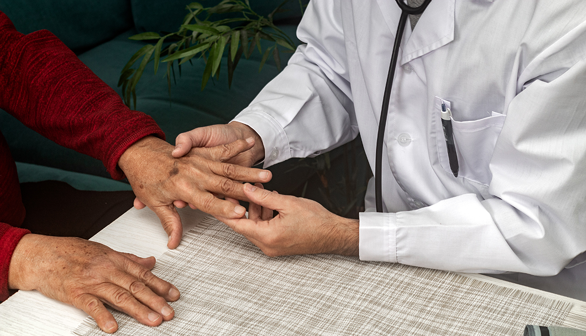 doctor examining the hand of a man.