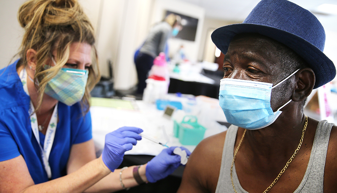 man receiving a covid vaccine at a vaccine site earlier this year