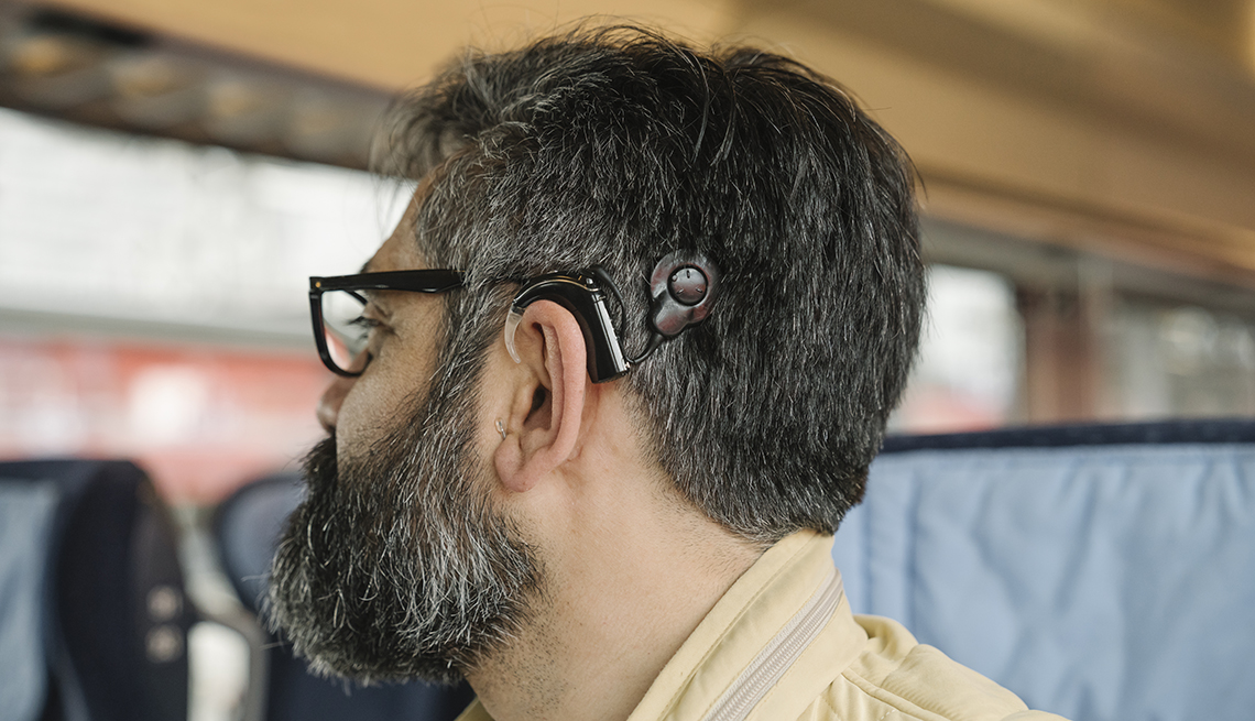profile of a man wearing a cochlear implant riding on a train