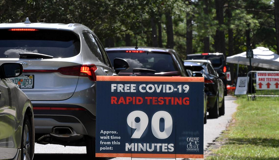 Personas hacen fila en sus vehículos para recibir la vacuna contra la COVID