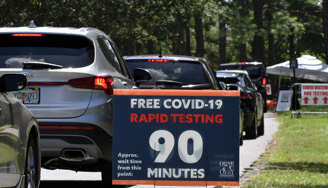 People in cars wait at a COVID-19 testing and vaccination site in Orlando, FL.