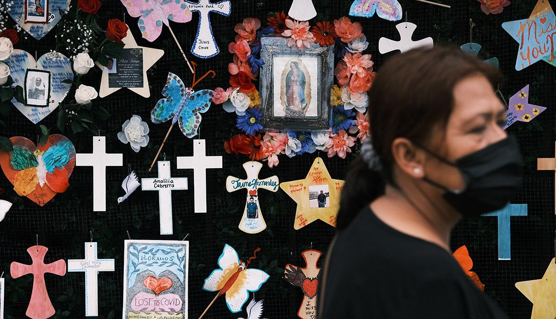 Una mujer camina frente a un memorial en honor a las víctimas de COVID