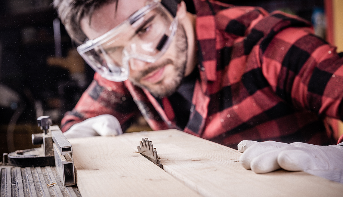 Male carpenter working with a wooden plank. He is wearing eye protection but not ear protection.