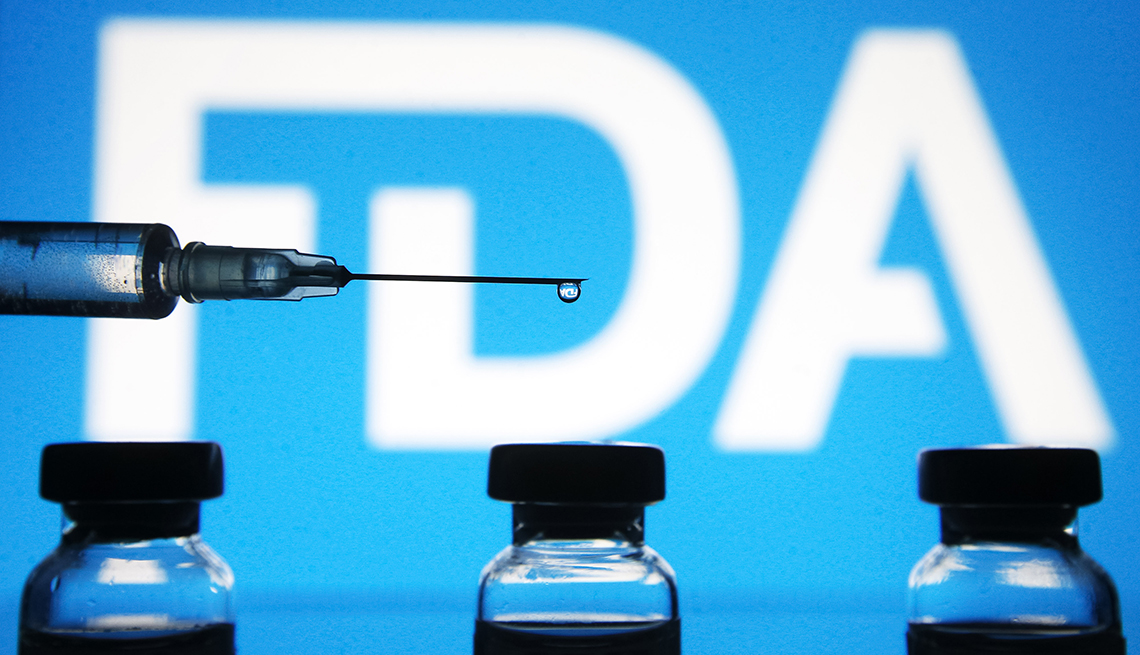 photo illustration a medical syringe and vials are seen in front of the Food and Drug Administration (FDA) logo