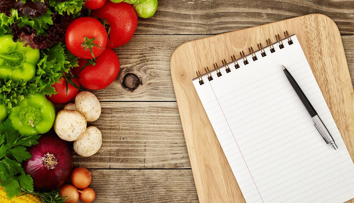 Una libreta de notas, un bolígrafo y vegetales sobre una mesa